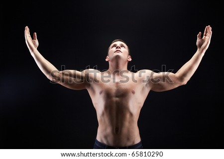 Image of shirtless man looking upwards with raised arms on black background - stock photo