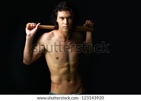 Image of shirtless man with bat looking at camera - stock photo