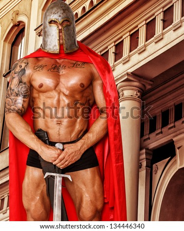 Image of shirtless warrior in pants, helmet and red mantle who is guarding building with sword - stock photo