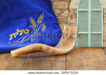 image of shofar (horn) and prayer case with word talit (prayer) writen on it in front of jerusalem ancient window. room for text. rosh hashanah (jewish holiday) concept . traditional holiday symbol.  - stock photo