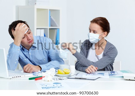 Image of sick businessman looking at his partner in mask offering him to put on one in office - stock photo
