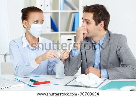 Image of sick businessman with tissue looking at his colleague in mask dissolving solution for him in office - stock photo