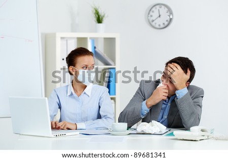 Image of sick businessman with tissue looking at laptop screen with his colleague in mask sitting near by in office - stock photo