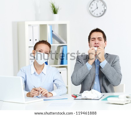 Image of sick businessman with tissue sneezing with his colleague in mask sitting near by and looking at camera in office - stock photo