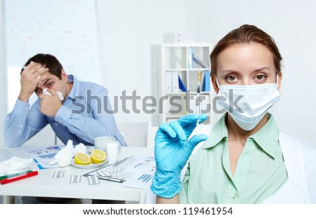Image of sick businessman working in office with nurse holding syringe on foreground - stock photo