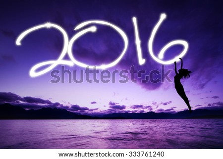 Image of silhouette woman jumping on the beach while drawing numbers 2016 on the air