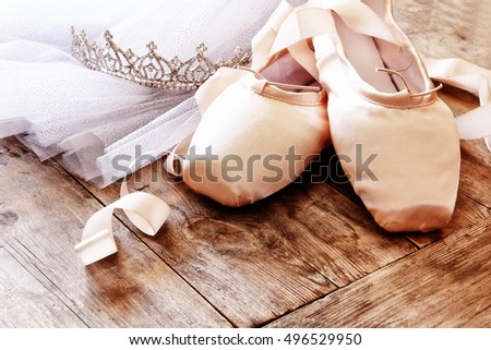 Image of silk pointe shoes and tutu on wooden floor. Vintage filtered