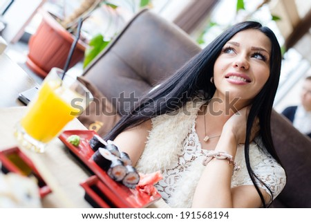 image of sitting in sushi restaurant or coffee shop beautiful sexy brunette girl young woman having fun happy smiling & looking up at copy space closeup portrait - stock photo