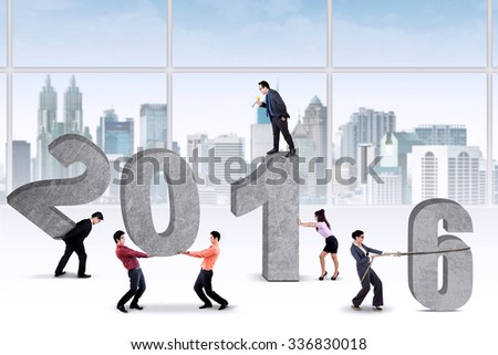 Image of six businesspeople working together to arrange numbers 2016 in the office - stock photo