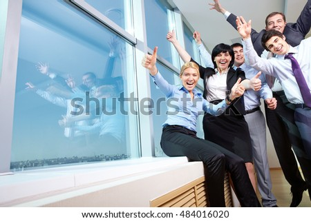 Image of six cheerful businesspeople at the window, screaming and showing thumbs