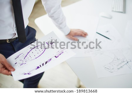 Image of sketch in hand businessman standing by workplace - stock photo