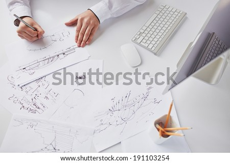 Image of sketches at workplace being drawn by businessman - stock photo