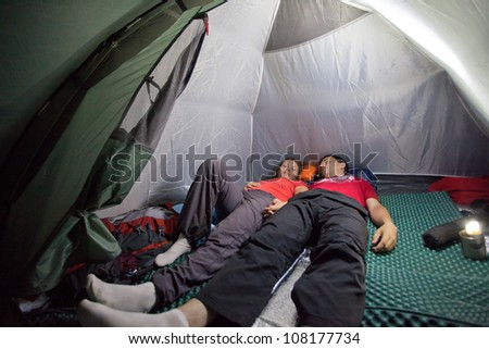 Image of sleeping tourists inside the tent camp on the background of night lighting flashlight in Almaty, Kazakhstan