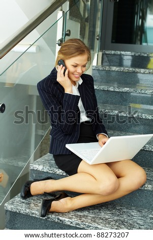 Image of smart businesswoman working on staircase with laptop and calling - stock photo