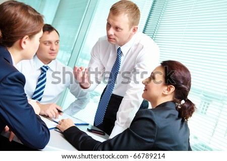 Image of smart employees looking at confident businessman while he explaining something in office - stock photo