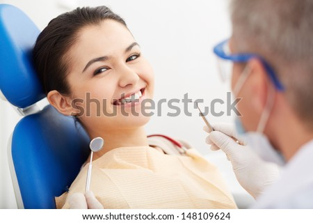 Image of smiling patient looking at camera at the dentist�¢??s