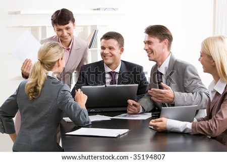 Image of smiling people watching at confident woman while she sharing her idea during meeting - stock photo