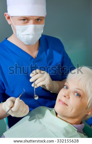 Image of  smiling  senior patient sitting on dental armchair with doctor