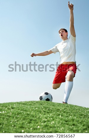 Image of soccer player shouting during game - stock photo