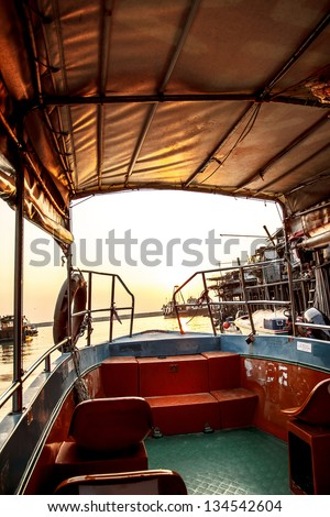 Image of some part of boat and bearly seen sunset - stock photo