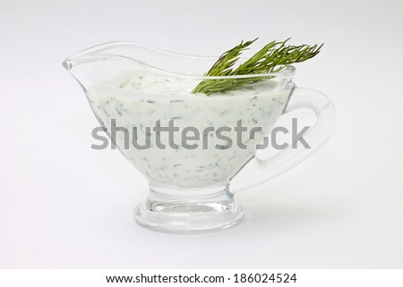Image of spicy cream sauce with dill in sauceboat - stock photo