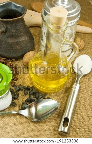 image of spoons, nuts, seeds,butter, salt shaker, coffee beans, a cup on a green background - stock photo