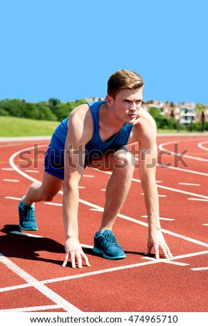 Image of sportsman starting to sprint in a stadium.