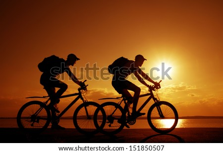 Image of sporty company couple - two friends on bicycles outdoors against sunset. Silhouette A lot phases of motion single cyclist along the shoreline coast Reflection on water Space for inscription