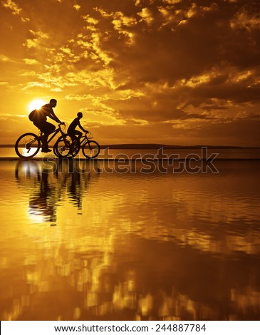 Image of sporty company friends on bicycles outdoors against sunset mountain. Silhouette of motion go of two 2 cyclist along shoreline coast Reflection sun on water Copy Space for inscription - stock photo