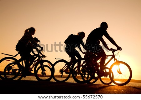 Image of sporty company  friends on bicycles outdoors against sunset. Silhouette - stock photo