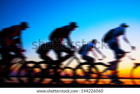 Image of sporty company friends on bicycles outdoors against sunset. Silhouette A lot phases of motion couple of cyclist along the shoreline coast - stock photo