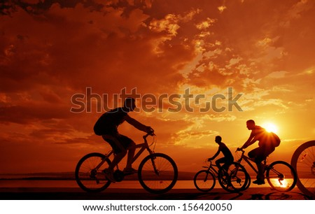 Image of sporty company friends on bicycles outdoors against sunset. Silhouette A lot phases of motion of a single cyclist along the shoreline coast Space for inscription - stock photo