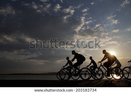 Image of sporty company friends on bicycles outdoors against sunset. Silhouette A lot phases of motion go of six 6 cyclist along shoreline coast Reflection sun on water Copy Space for inscription