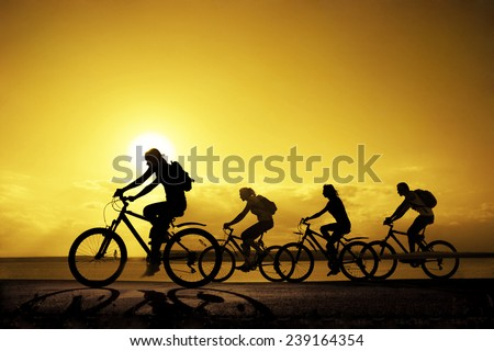 Image of sporty company friends on bicycles outdoors against sunset. Silhouette A lot phases of motion go of four 4 cyclist along shoreline coast Reflection sun on water Copy Space for inscription