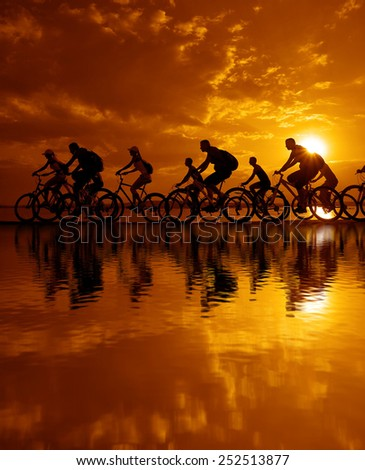 Image of sporty company friends on bicycles outdoors against sunset. Silhouette A lot phases of motion go of ten 10 cyclist along shoreline coast Reflection sun on water Copy Space for inscription