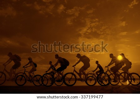 Image of sporty company friends on bicycles outdoors against sunset. Silhouette A lot phases of motion go of eight 8 cyclist along shoreline coast Reflection sun on water Copy Space for inscription