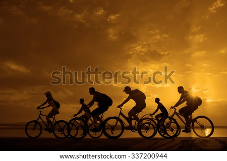 Image of sporty company friends on bicycles outdoors against sunset. Silhouette A lot phases of motion go of six 6 cyclist along shoreline coast Reflection sun on water Copy Space for inscription - stock photo