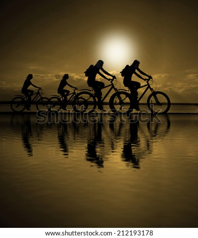 Image of sporty company friends on bicycles outdoors against sunset. Silhouette two phases of motion go of four 4 cyclist along shoreline coast Reflection sun on water Copy Space for inscription