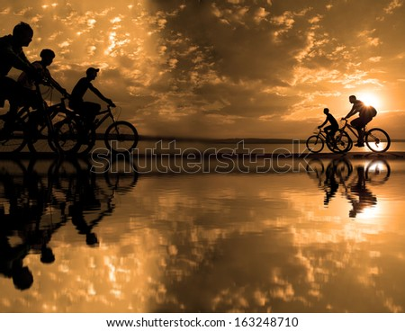 Image of sporty company friends on bicycles outdoors against sunset Silhouette with .  cyclist along the shoreline coast Space for inscription - stock photo