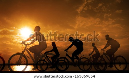 Image of sporty company friends on bicycles outdoors against yellow sunset background Silhouette A lot phases of motion cyclist along shoreline coast  Space for inscription