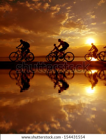 Image of sporty company six friends on bicycles outdoors against sunset. Silhouette A lot phases of motion of a single cyclist along the shoreline coast Reflection on water Space for inscription - stock photo