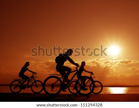 Image of sporty company three friends on bicycles outdoors against sunset. Silhouette A lot phases of motion of a single cyclist along the shoreline coast Reflection on water Space for inscription