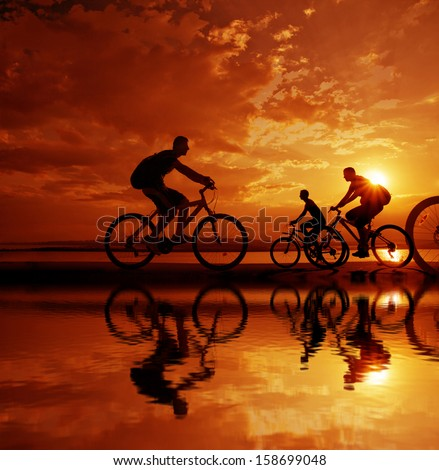 Image of sporty company three friends on bicycles outdoors against sunset. Silhouette A lot phases of motion of a single cyclist along the shoreline coast Reflection on water Space for inscription - stock photo