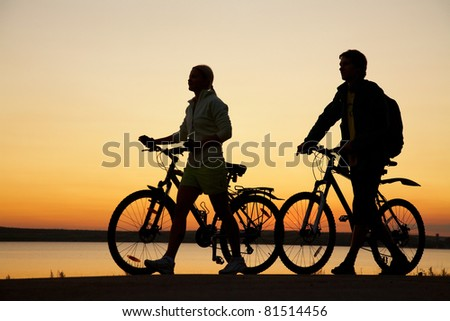 Image of sporty couple with bicycles walking  outdoors against sunset. Silhouette. - stock photo