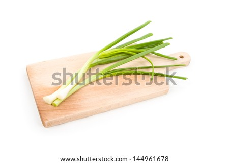 Image of spring onion on cutting board isolated on white - stock photo