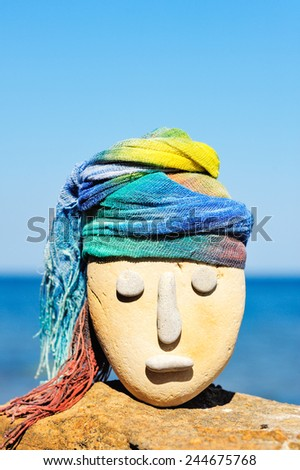 Image of stone head with a coloured bandana - stock photo