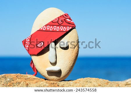 Image of stone head with a patterned red bandana - stock photo