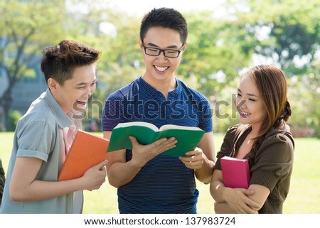 Image of students reading a joke in their book - stock photo