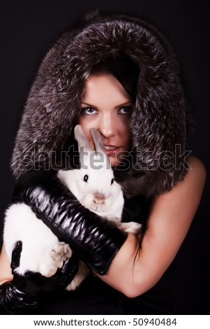 Image of stylish girl with her rabbit - stock photo