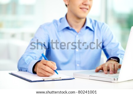 Image of successful businessman typing and making notes